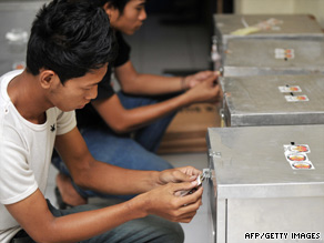 Volunteers in Jakarta seal ballot boxes before officials send them to voting stations.