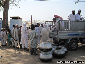 A line forms at a refugee camp in Pakistan's Swabi district. Plans call for people in camps to return first.