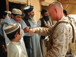 A US Marine walks by an Afghan farmer in the Garmsir district of Helmand Province on July 12.