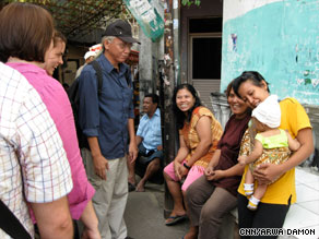 "Ronny Poluan (in cap), who runs ""Jakarta Hidden Tours,"" takes a group through a Jakarta slum."
