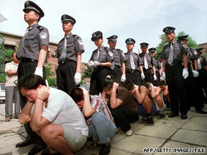 Chinese police guard a group of prisoners outside a Beijing court on May 25, 2001, before their sentencing.