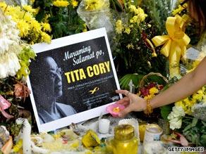 Filipinos light candles outside the home of Corazon 'Cory' Aquino in suburban Quezon city.