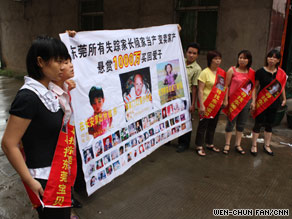 Parents outside the home of activist Deng Huidong in southeast China, hold banners with pictures of abducted children.