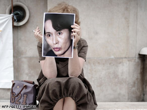 A woman holds up a portrait of Aung San Suu Kyi at a Paris rally calling for her release.