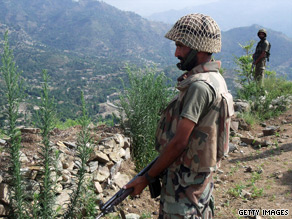 Pakistani soldiers look on from a mountain during a patrol in the troubled area of Maidan.
