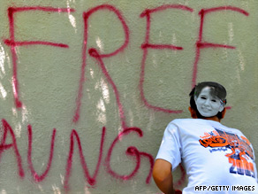 A Myanmar protester sprays grafitti on the wall of the Myanmar embassy in New Delhi Wednesday.