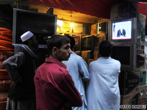 Afghans watch a live televised election debate in a street in Kabul on Sunday.