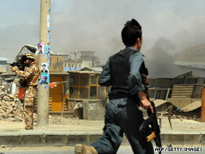An Afghan police officer runs toward the scene of a car bomb Tuesday as a NATO soldier aims his weapon.