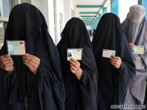 Burqa-clad women display ID cards as they queue to vote in Kandahar on Thursday.