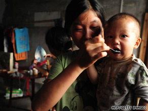 A mother feeds her child in a village near the Wugang Manganese Smelting Plant in Hunan province.