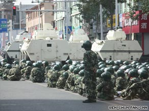 People's Armed Police units equipped with armored personnel carriers take positions in Urumqi on Saturday.