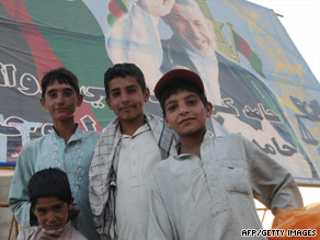 Afghan children stand in front of a billboard of President Hamid Karzai in Kabul on Sunday.