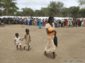 A Tamil mother walks with her children as civilians wait for food at the Manik Farm refugee camp, May 26, 2009.