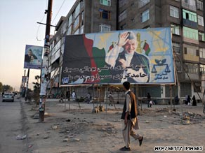 A man walks past a billboard with a photo of Afghanistan's President Hamid Karzai in Kabul on September 6, 2009.