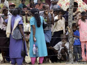 Tamil civilians, pictured in May, stand behind a barbed-wire fence at a refugee camp near the northern Sri Lankan town of Vavuniya.