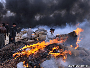 A U.S. marine stands guard over a burning pile of opium poppy seeds in Helmand Province.