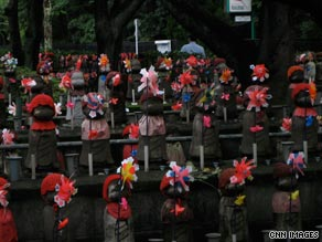Tiny statues of Jizo, a Japanese deity lines the gardens of the Zojoji temple in Tokyo.