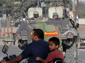 A NATO armored vehicle escorts a convoy of supply trucks Friday in Kabul, Afghanistan.