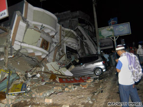 A resident stands next to building that collapsed onto a car in Padang, Indonesia, on Wednesday.