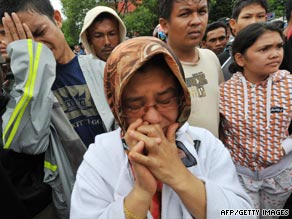 Family members mourn in front of a collapsed school in Padang on Thursday.