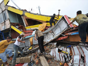 People search the rubble of a collapsed shop in Padang, Indonesia.