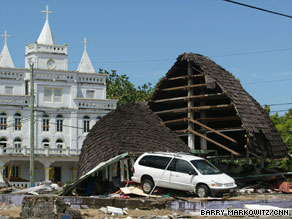 Debris clutters a road Tuesday in Pago Pago. At least 139 people have been confirmed dead.
