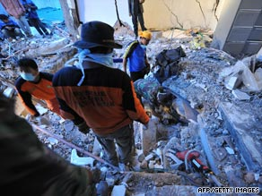 Indonesian soldiers crawl under the rubble of a collapsed building to search for victims.