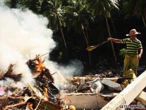 A man throws rubble onto a fire burning on what used to be his parents' home in Samoa.