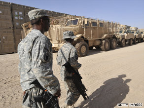 U.S. troops walk past a group of armored vehicles on Saturday at a military base in Afghanistan.