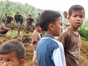 Children stand near to soldiers helping with the recovery of bodies in the village.