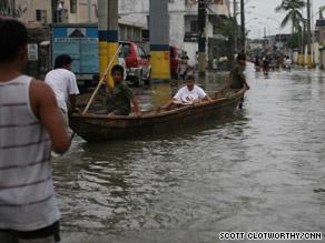 People use a canoe to cross floodwaters in Manila's Laguna de Bay neighborhood.