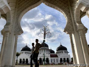 Teenagers walk past one of the main mosques in the staunchly Muslim region of Aceh.