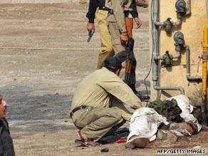 A bomb disposal squad member removes a suicide jacket from a body at the FIA in Lahore on Thursday.