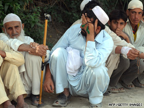 Displaced Pakistanis wait in line Monday after fleeing military operations against militants in South Waziristan.