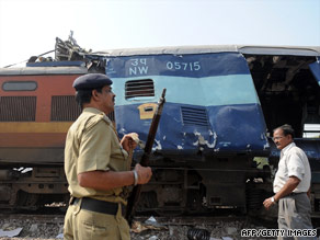Indian Railway Protection Force personnel look at a damaged carriage after the collision Wednesday.