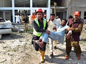 Rescuers carry an injured man from the site of the bomb blast in Pakistan.
