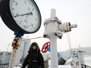 A woman passes in front of a manometer set on a gas pipe in the Ukrainian city of Boyarka, near Kiev.