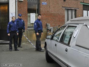 Police look at a hearse parked in front of the childcare centre in Dendermonde where the attack took place.