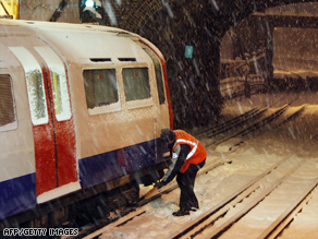 An underground worker attempts to release part of a tube train which had frozen in west London.