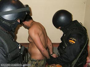 Spanish police detain a suspect following the arrests in Valencia and Barcelona Tuesday.