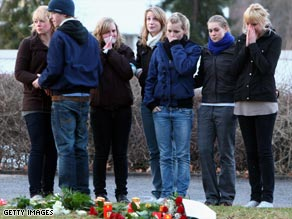 People lay flowers at the school Wednesday.