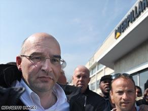 Caterpillar plant director Nicolas Polutnik (left) leaves the building after the 24-hour protest.