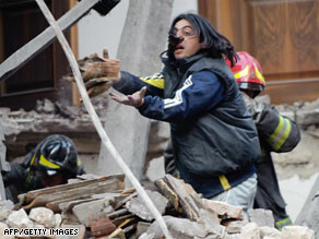 Rescue workers search for survivors in the ruins of a collapsed house in L'Aquila, Italy.