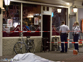 Police officers stand next to the body of the victim killed by the cafe gunman in Rotterdam.
