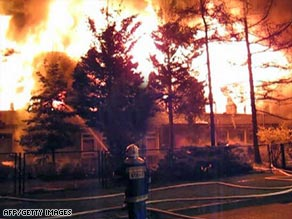 A firefighter struggles to control the raging fire at the homeless shelter in Poland.