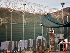 A guard leans on a fence talking to a detainee at Guantanamo earlier this year.