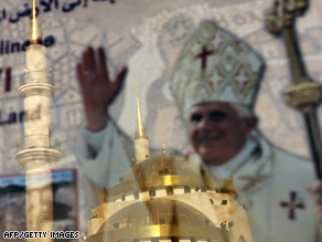A mosque in Madaba, Jordan, is reflected in a shop window with a picture of Pope Benedict Thursday.