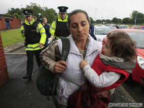 A Romanian woman and her child are escorted by police in Belfast on Wednesday.