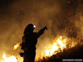 A firefighter walks around the area where a fire burns in Andorra early on July 23, near Teruel.