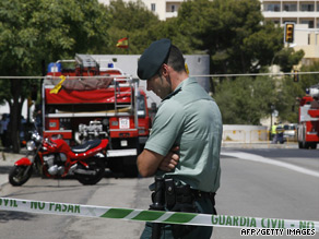 A civil guard officer stands on duty while wounded are evacuated from the barracks in Mallorca.